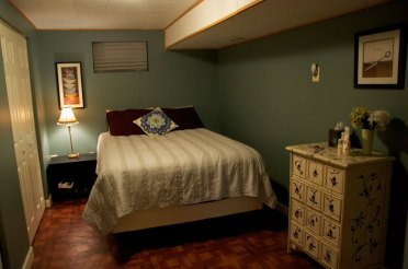 Traditional-dresser-and-wide-bed-inside-rustic-basement-bedroom-ideas-with-brown-flooring