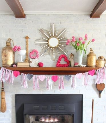 A-bright-and-white-valentine-mantel-with-a-heart-and-tassel-garland-pink-blooms-pink-hearts-and-gold-touches