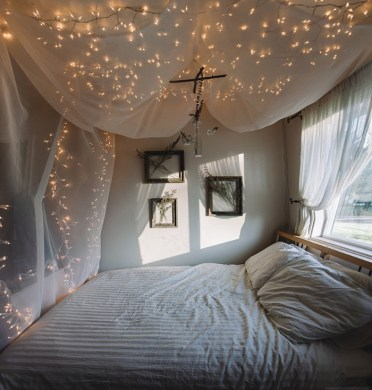 Baldachin-made-from-sheer-white-fabric-and-decorated-with-multiple-lit-string-lights-over-a-bed-teenage-bedroom-ideas-for-small-rooms-window-and-three-framed-bouquets-of-dried-flowers