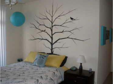Mural-of-a-tree-with-bare-branches-and-two-birds-painted-in-black-on-a-cream-wall-near-a-bed-with-yellow-and-blue-cushions-and-a-dark-brown-bedside-table
