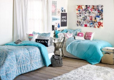 Room-for-sisters-with-a-wooden-floor-and-a-fluffy-pale-grey-rug-two-beds-with-blue-covers-ideas-for-teen-bedrooms-white-walls-with-posters-and-a-board-with-photos