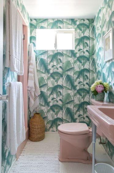 A-bright-tropical-bathroom-with-tropical-wallpaper-a-pink-sink-and-toilet-neutral-linens