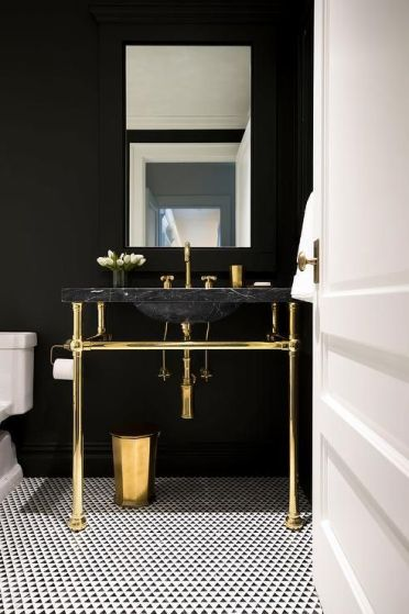 A-chic-powder-room-with-black-walls-a-black-marble-sink-gold-fixtures-and-legs-plus-a-mosaic-tile-floor