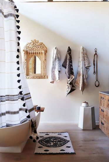 A-neutral-bathroom-with-a-boho-rug-a-curtain-with-tassels-printed-towels-and-an-ornate-mirror