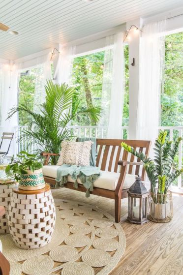 1-a-tropical-boho-porch-with-wooden-furniture-jute-rugs-lots-of-potted-greenery-and-candle-lanterns