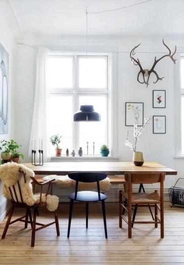 16 sedie colorate con pavimento in legno chiaro e una nera per un mix audace e chic