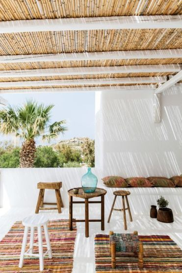 2-12-a-tropical-terrace-with-colorful-boho-rugs-wooden-stools-and-a-table-some-pillows-and-potted-grreenery