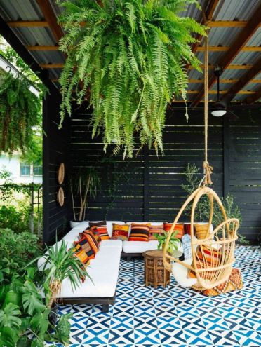 2-15-a-beautiful-tropical-patio-with-a-roof-and-greenery-hanging-down-with-an-l-shaped-sofa-with-colorful-pillows-a-rattan-chair-and-a-mosaic-tile-floor