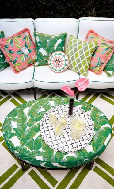 2-26-make-up-a-boho-patio-with-a-large-neutral-sofa-with-colorful-pillows-and-a-tropical-leaf-print-table