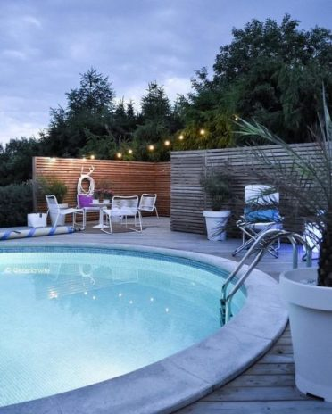 5-a-welcoming-contemporary-space-with-metal-furniture-and-a-large-round-pool-with-inner-lights-looks-inviting