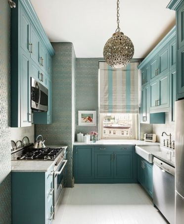A-beautiful-turquoise-kitchen-with-white-countertops-a-window-instead-of-a-backsplash-and-vintage-faucets