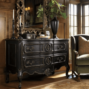 05-a-dark-wood-sideboard-with-antique-decor-a-mirror-and-a-dark-vase