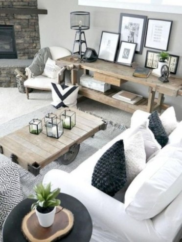 2-a-stylish-farmhouse-living-space-with-rough-wooden-tables-white-upholstery-some-prints-and-a-faux-stone-clad-fireplace