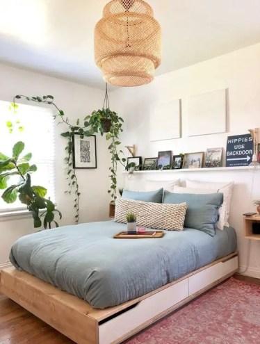Una-piccola-camera-da-letto-contemporanea-con-un-letto-contenitore-una-sporgenza-con-una-galleria-parete-una-lampada-di vimini-e-vegetazione-in vaso