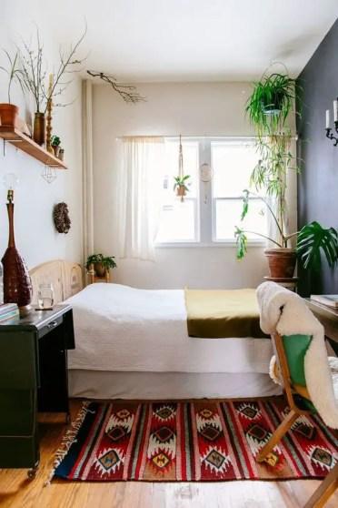 Una-piccola-camera-boho-con-un-letto-in-legno-scrivania-e-sedia-boho-tessuti-piante in vaso e-alcuni-tocchi di vimini