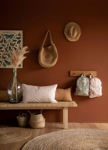 02-a-boho-entryway-with-a-terracotta-wall-a-woven-bench-and-a-rack-some-baskets-and-pampas-grass-in-a-large-bottle