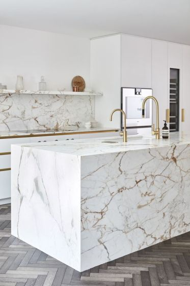 09-a-modern-luxurious-kitchen-with-white-cabinets-a-white-marble-kitchen-island-and-a-backsplash-plus-gold-fixtures