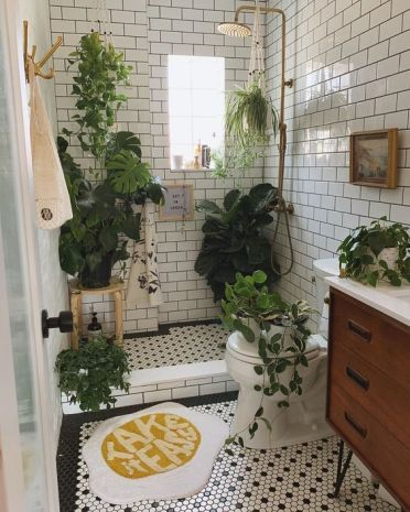 2-a-small-and-neutral-bathroom-with-a-wooden-vanity-lots-of-greenery-in-pots-and-some-suspended-plants
