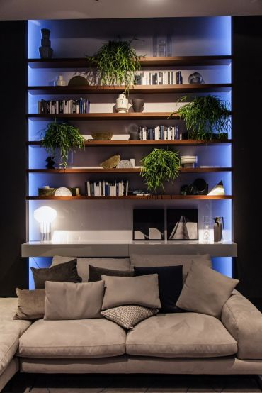 Floating-shelvrs-above-living-room-sofa-with-led-blue-light-and-decorated-with-plants-and-books