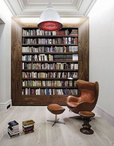 A-modern-home-library-with-a-bookcase-in-a-wide-wooden-frame-with-a-comfy-leather-chair-and-a-red-pendant-lamp
