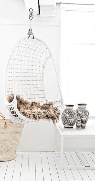 07-a-white-wicker-hanging-chair-with-faux-fur-for-a-scandinavian-interior