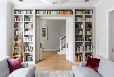 1-bookshelf-that-wraps-itself-around-the-doorway-helps-create-a-lovely-wall-of-books-in-the-living-room-with-ample-natural-light