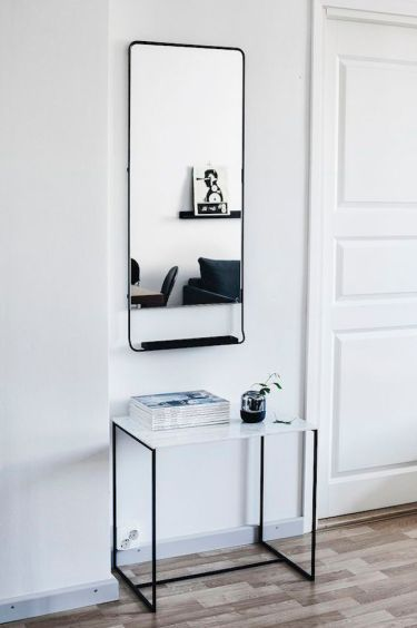 A-scandinavian-entryway-with-striking-charcoal-tones-for-the-mirror-and-table