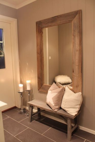 Large-framed-mirror-hung-above-rustic-wood-bench