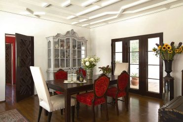Lovely-hutch-adds-classic-charm-to-the-traditional-dining-space-with-colorful-red-chairs