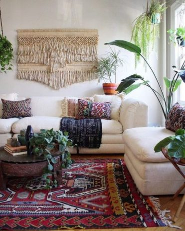 A-colorful-boho-living-space-with-a-macrame-hanging-a-boho-rug-and-pillows-potted-greenery-and-neutral-furniture