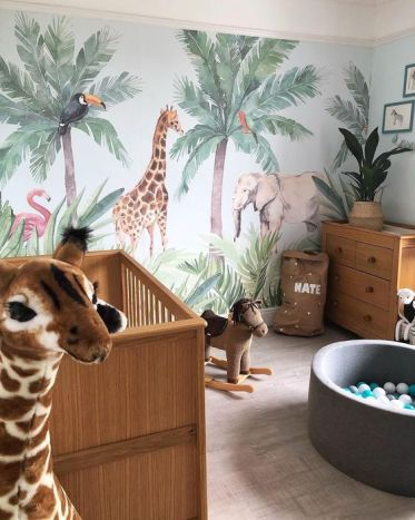 A-jungle-themed-nursery-with-a-statement-animal-wall-animal-toys-potted-plants-and-cute-furniture