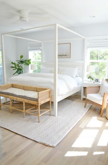 A-stylish-modern-neutral-bedroom-with-a-white-canopy-bed-a-woven-bench-chairs-and-neutral-textiles