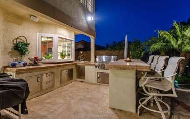 Outdoor-kitchen-with-bar-stool-seating-on-stone-patio