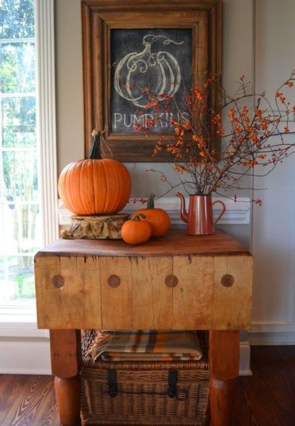 04-an-entryway-console-with-orange-pumpkins-some-branches-with-berries-and-a-wicker-chest