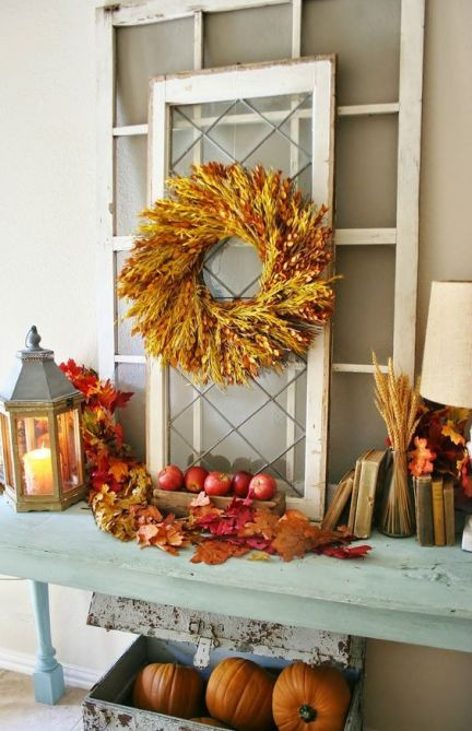 09-a-console-table-with-fall-apples-leaves-wheat-spikes-a-spike-wreath-and-some-pumpkins-under-the-table