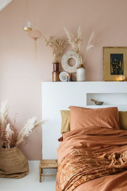 36-an-inviting-boho-bedroom-with-a-pale-brown-wall-a-bed-with-terracotta-bedding-grasses-in-vases-and-candles-is-cool