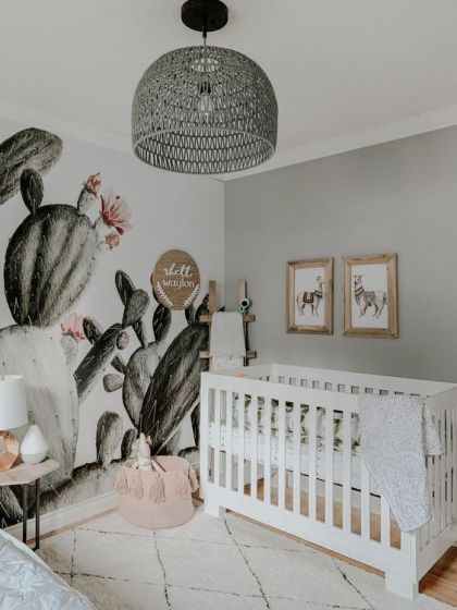 A-boho-desert-nursery-with-a-cactus-wall-a-pink-tassel-basket-a-grey-rattan-lamp-and-llama-artworks-over-the-crib