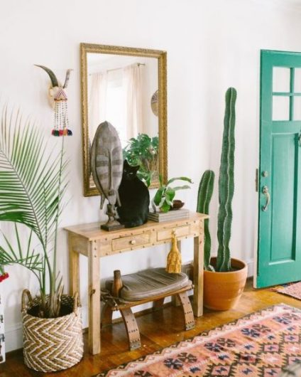 A-bright-boho-entryway-with-a-sleek-wooden-console-a-catchy-stool-that-matches-potted-plants-a-mirror-in-an-arnate-frame-and-some-boho-art