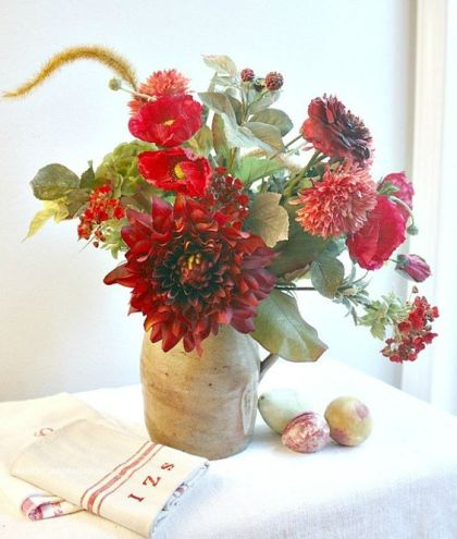A-bright-fall-centerpiece-of-red-and-burgundy-blooms-greenery-in-a-vintage-jug-is-a-bold-decoration