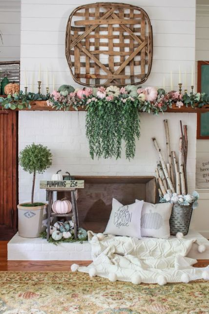 A-bright-fall-mantel-with-cascadign-greenery-pastel-pumpkins-greenery-branches-in-a-bucket-and-a-wooden-basket-1