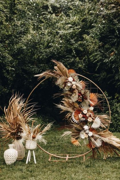 A-chic-modern-boho-wedding-arch-decorated-with-dried-colorful-leaves-and-fronds-and-pastel-blooms