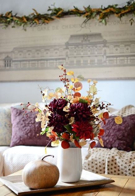 A-colorful-fall-arrangement-of-leaves-branches-with-berries-faux-bright-blooms-and-a-large-veggie-next-to-it