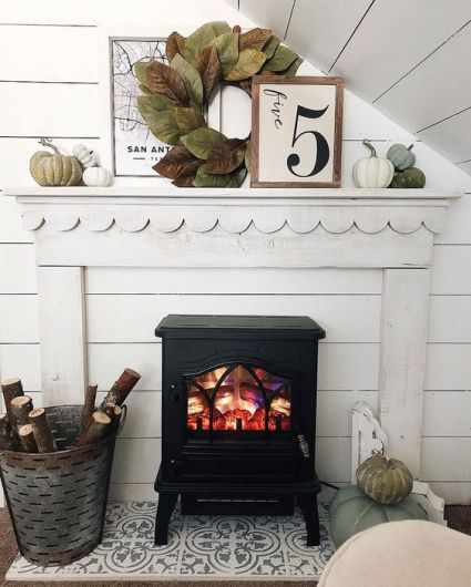 A-cozy-fall-mantel-with-a-large-leaf-wreath-muted-pumpkins-and-branches-in-the-bucket