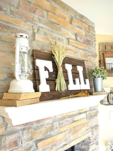 A-dark-stained-fall-sign-with-white-letters-and-a-pack-of-wheat-right-in-the-center-for-a-rustic-touch