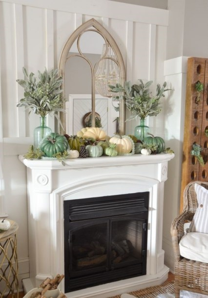 A-fall-mantel-decorated-with-pinecones-faux-pumpkins-pale-greenery-in-tall-bottles-2