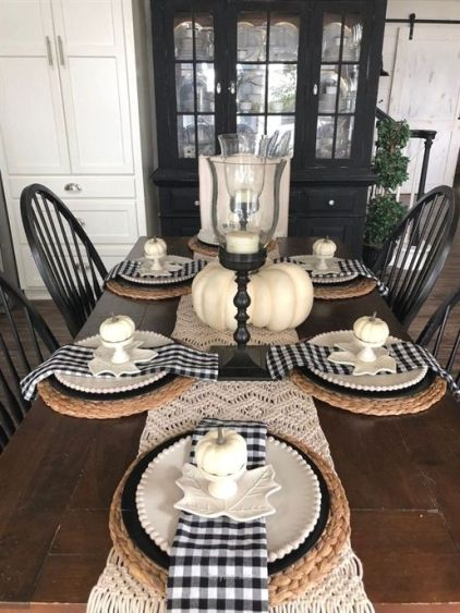 A-farmhouse-fall-table-setting-with-a-macrame-runner-woven-placemats-plaid-napkins-and-fake-pumpkins