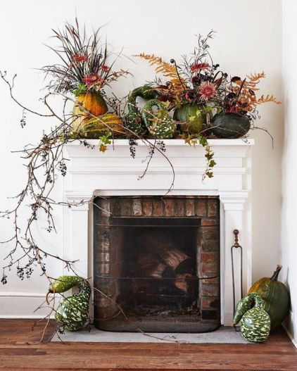 A-lush-harvest-mantel-decorated-with-greenery-long-branches-and-pumpkins-and-gourds-on-the-mantel-1