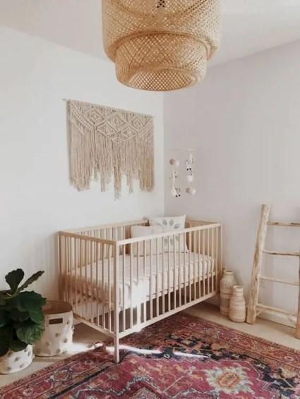 A-minimal-boho-nursery-with-a-large-macrame-a-wicker-lamp-a-boho-rug-some-vases-and-baskets-for-storage