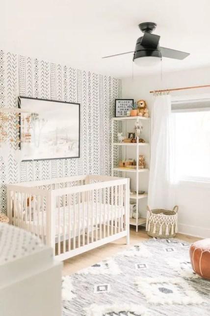 A-neutral-boho-nursery-with-a-printed-wall-a-printed-rug-a-leather-ottoman-a-white-crib-and-a-woven-basket