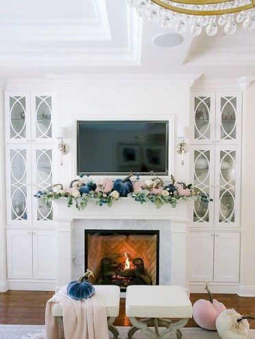 A-pastel-fall-mantel-with-blush-and-navy-velvet-pumpkins-and-fresh-greenery-is-a-cool-modern-idea-1